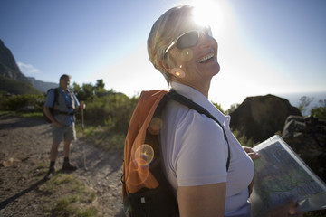 Mature couple, with rucksacks, hiking on mountain trail in bright sunlight, focus on woman holding map, smiling (lens flare)
