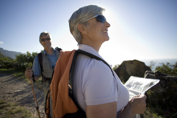 Mature couple, with rucksacks, hiking on mountain trail, man holding hiking pole, woman using map, smiling