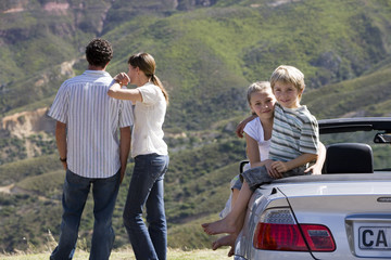 Couple looking at mountain scenery, two children (6-9) sitting in parked convertible car at roadside, smiling, portrait