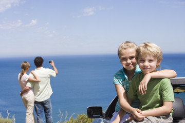 Parents photographing Atlantic Ocean from clifftop, focus on children (6-9) sitting in parked convertible, portrait