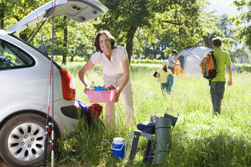 Family unloading car on camping trip, focus on woman holding pink container beside car boot, smiling, portrait