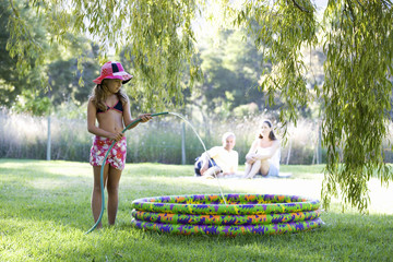 Young girl filling a paddling pool from a garden hose