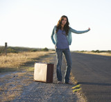 A woman with a suitcase hitching a lift