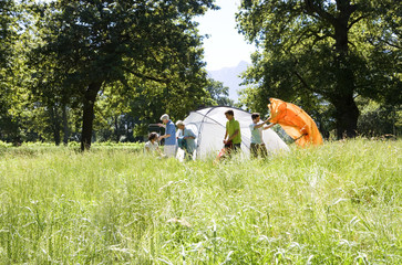 Multi-generational family setting up tent on camping trip in rural setting