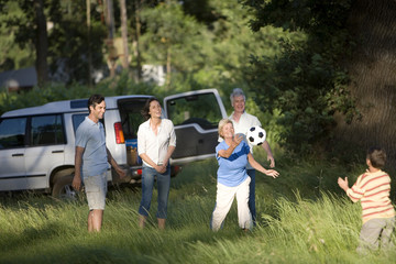 Multi-generational family playing with soccer ball in woodland clearing on camping trip