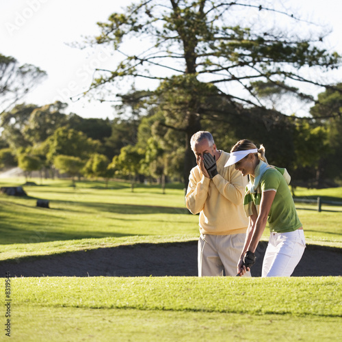Man teaching a woman how to play golf
