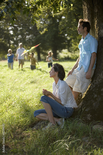 Grandparents and grandchildren (7-10) playing with kite in woodland clearing, parents resting by tree in foreground