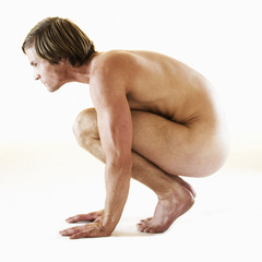 A male nude, crouching