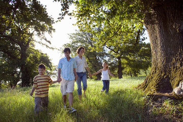 Family walking hand in hand along woodland trail, smiling, front view