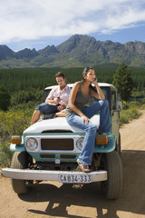 Young couple sitting on bonnet of parked jeep on dirt track in mountain valley, man using mobile phone