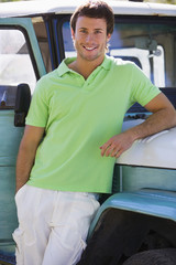Young man, in green polo shirt, leaning against parked jeep, smiling, portrait