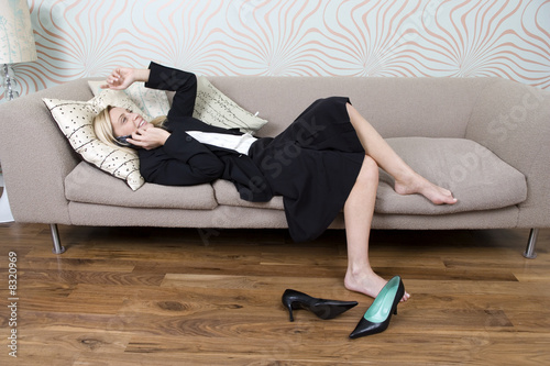 Businesswoman laying on a sofa talking on the phone