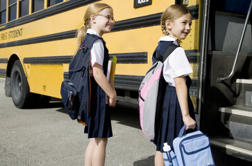 Two schoolgirls getting on a school bus