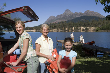 Girl (8-10) unloading life jackets from SUV with mother and grandmother, rest of family on lake jetty beside boat