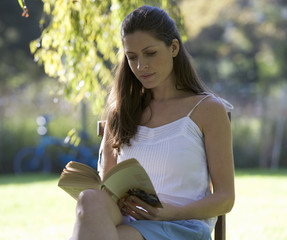 A woman sitting in the garden reading a book