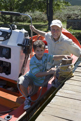 Grandfather and grandson (8-10) sitting in motorboat at lake jetty, boy tying rope to mooring post, portrait
