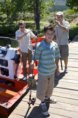 Boy (8-10) standing on lake jetty with fishing rod, father and grandfather loading motorboat in background