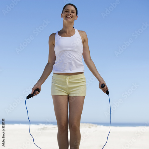 A young woman skipping on a beach