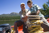 Grandfather and grandson (8-10) standing in motorboat beside lake jetty, tying rope to mooring post