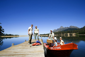 Multi-generational family loading motorboat with provisions at lake jetty, grandfather holding picnic hamper