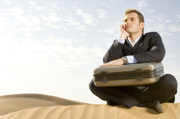 A man with a suitcase sitting in a desert