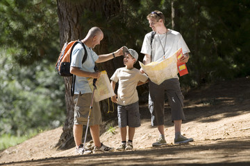 Boy (8-10) hiking on woodland trail with father and grandfather, man consulting map, smiling