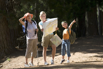Girl (7-9) hiking on woodland trail with mother and grandmother, pointing, woman consulting map, smiling