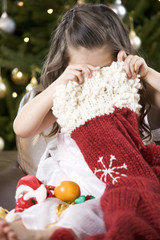 A young girl delving into a Christmas stocking
