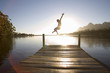 Man jumping from jetty into lake at sunset, rear view (lens flare, backlit)