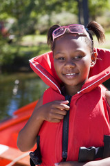 Girl (7-9) wearing red life jacket, smiling, close-up, portrait