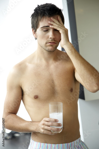 Young man drinking a hangover remedy