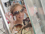 Teenage girl (14-16) trying on sunglasses from display rack in shop, smiling, close-up (tilt)