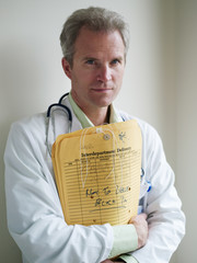 Mature doctor, in laboratory coat, holding medical files, portrait