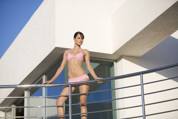 A woman in a bikini standing on a balcony