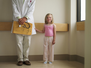 Girl (6-8) standing beside doctor in hospital, man with medical files, girl tugging on laboratory coat, smiling, portrait