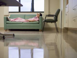 Nurse taking break in hospital staff room, lying on sofa, hands behind head, side view