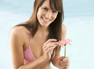 A young woman in a bikini holding a flower