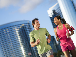 Couple, in sportswear, jogging in park, listening to MP3 players strapped to arms, smiling (tilt)