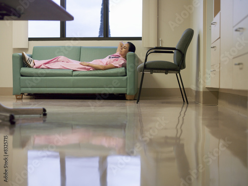 Nurse taking break in hospital staff room, lying on sofa, hands behind head, side view