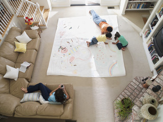 Family drawing on large piece of paper laid out on living room floor, overhead view