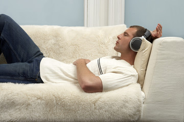 Young man listening on music through headphones