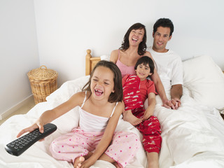 Family sitting on double bed at home, watching television, girl (5-7) using remote control, laughing