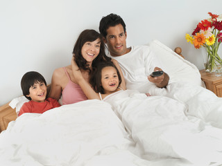 Family sitting in double bed at home, watching television, man using remote control