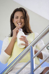 A woman drinking milk through a straw