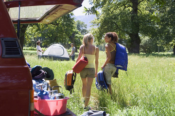 Two young women unloading parked SUV in woodland clearing on camping trip, rear view, smiling
