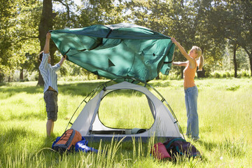 Young couple assembling dome tent on camping trip in woodland clearing, side view