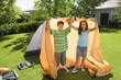 Brother and sister (8-10) assembling dome tent on garden lawn, holding orange outer tent canvas above heads, smiling, portrait