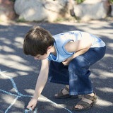 Young boy writing in chalk on the playground