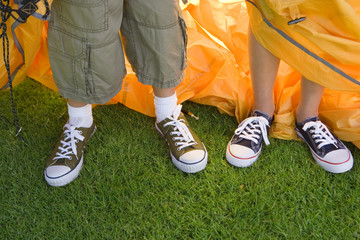 Brother and sister (8-10) assembling dome tent on garden lawn, standing beside orange outer tent canvas, low section, close-up, front view