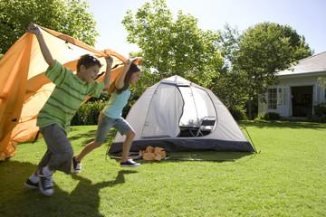 Brother and sister (8-10) running with trailing orange outer tent canvas past incomplete dome tent on garden lawn, smiling, side view
